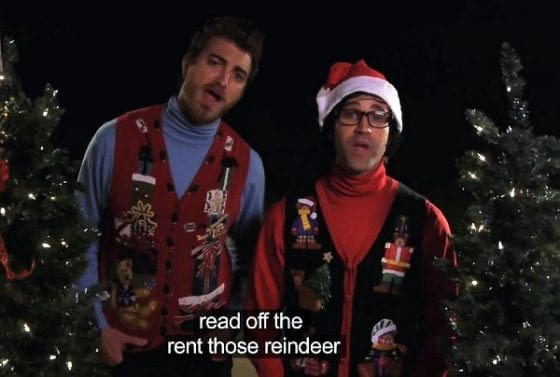 """Two men appearing to sing """"Rudolph the Red Nosed Reindeer"""" with closed-caption words """"read off the rent those reindeer."""""""